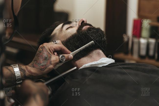 Barber combing client's beard at salon
