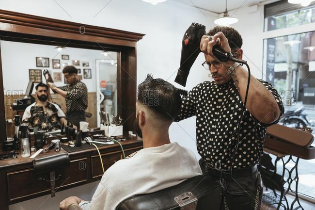 Trendy hairdresser blow drying man's hair at salon