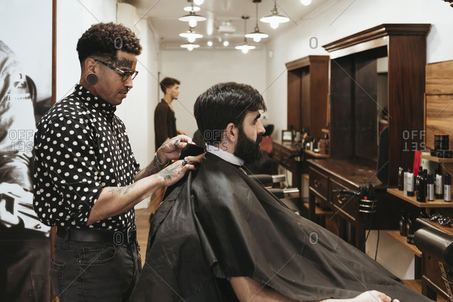 Trendy barber fixing cape on male client at salon