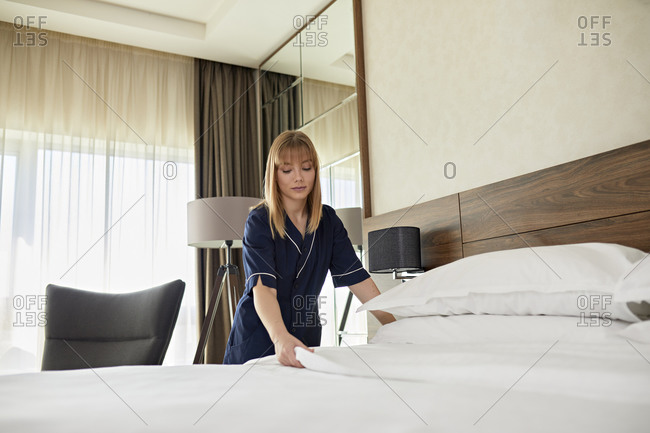 Chambermaid arranging sheet on bed in hotel room