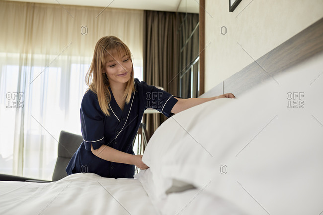 Smiling chambermaid arranging pillows on bed in hotel room