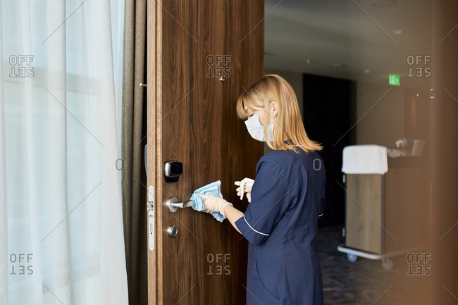 Chambermaid wearing mask cleaning doorknob in hotel