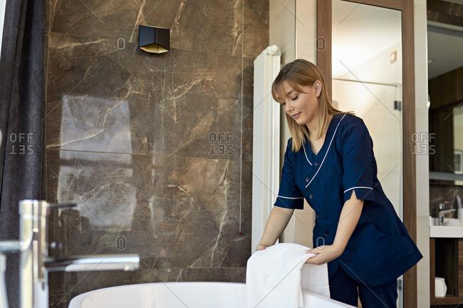 Chambermaid placing towel on bathtub while standing in hotel bathroom