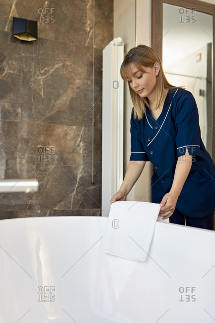 Chambermaid placing towel on bathtub while standing in bathroom