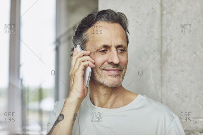 Portrait of a senior man on the phone in a loft flat