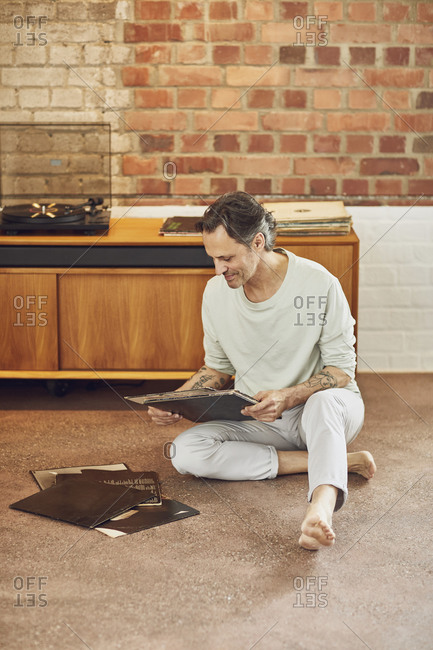 Senior man in a loft flat looking at records