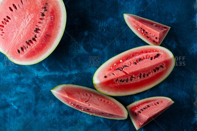 Overhead view of sliced watermelon on dark blue surface