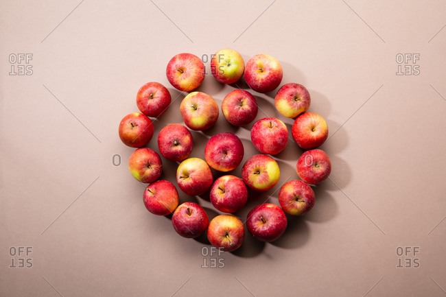 Overhead view of red apples arranged on a light brown surface