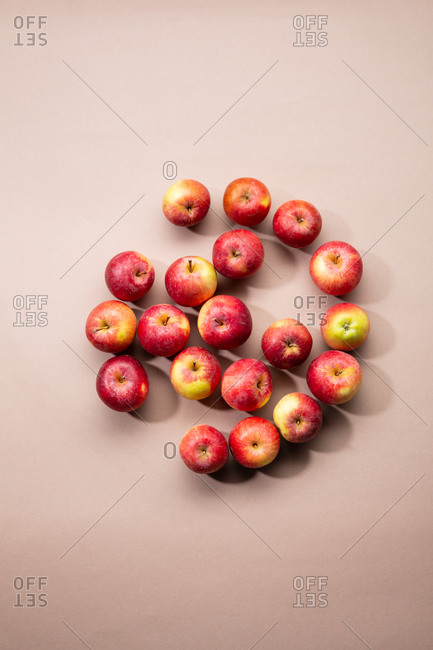 Overhead view of fresh red apples on brown surface