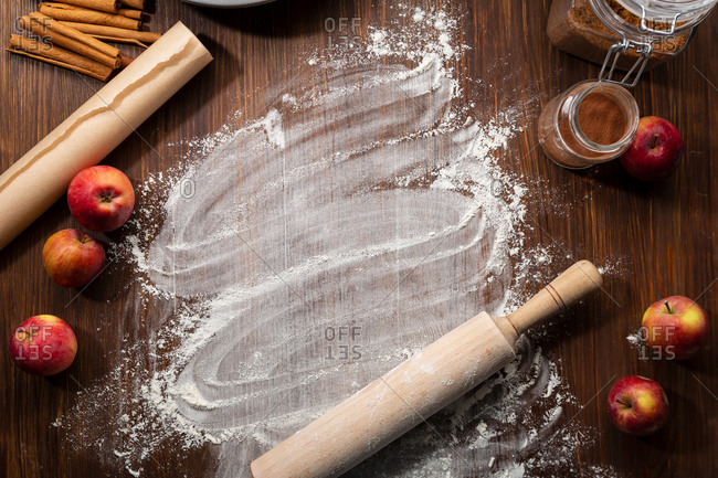Wooden table with flour and apples