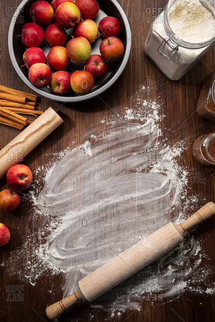 Wooden table with flour and apple in baking dish