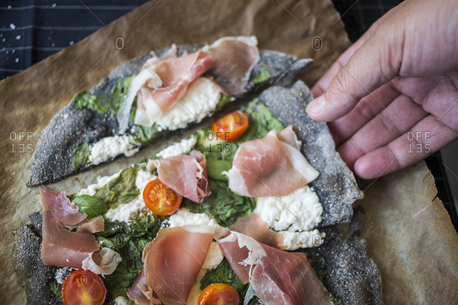 Person grabbing a slice of black pizza with spinach, prosciutto, tomatoes and homemade goat cheese