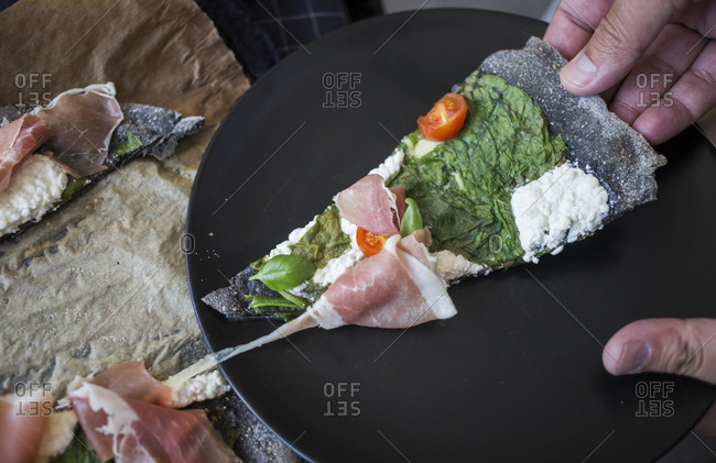 Hand holding a slice of black pizza with spinach, prosciutto, tomatoes and homemade goat cheese on a black plate