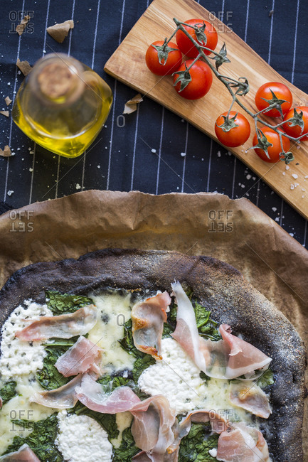 Black pizza with spinach, prosciutto and homemade goat cheese on a dark striped background