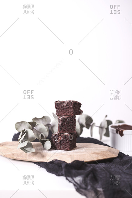 Homemade brownie with roasted hazelnuts and melted chocolate stacked on a wooden board