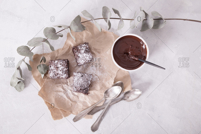 Overhead view of homemade brownie with powdered sugar and melted chocolate