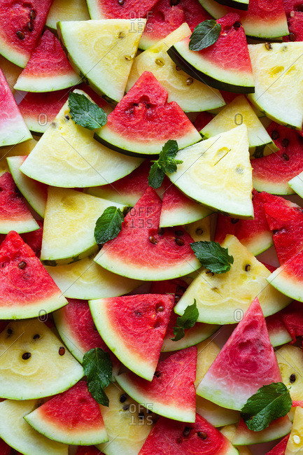 Fresh sliced organic pink and yellow watermelon triangles and mint leaves