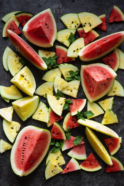 Fresh sliced organic watermelon on dark background with mint leaves