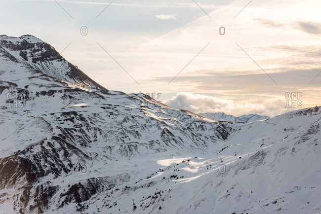 Severe cold winter landscape with snowy rocky mountain peaks and sunlight breaking through