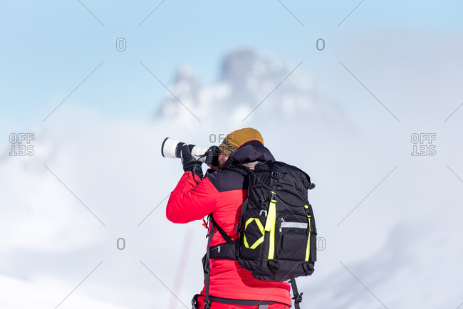 Back view of unrecognizable in red warm outfit and ski boots and with backpack taking photos with professional equipment on mountain slope in sunlight