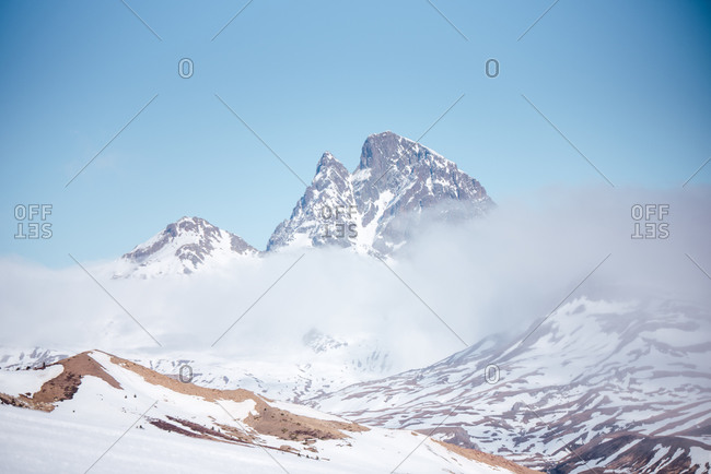 Severe cold winter landscape with snowy rocky mountain peaks with dense fog