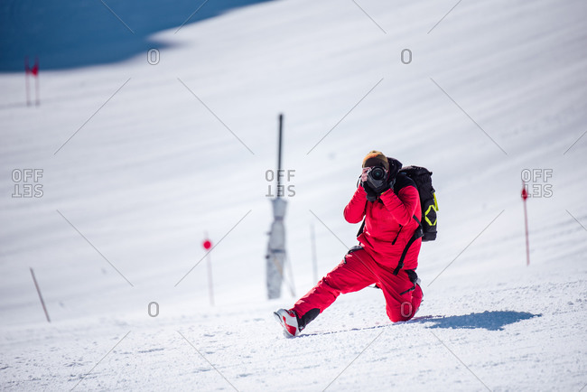 Unrecognizable man in red warm outfit and ski boots and with backpack taking photos looking at camera with professional equipment on mountain slope in sunlight