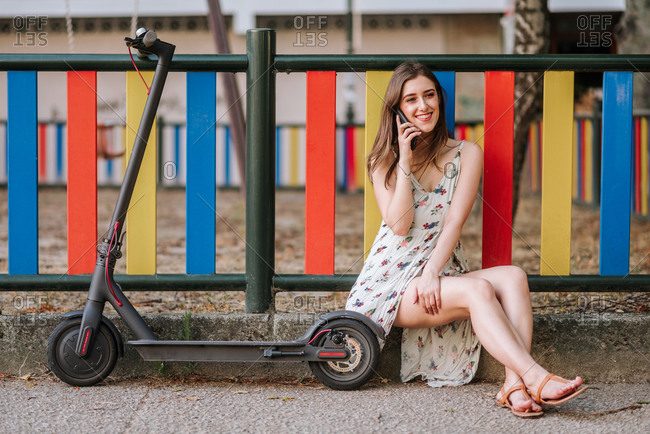 Positive female wearing summer dress sitting on stone border near electric scooter and having conversation on smartphone