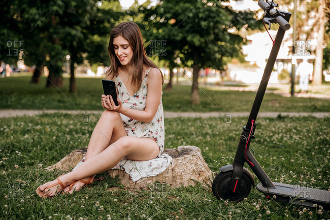 Delighted female in summer dress sitting on stump in garden and resting after riding electric scooter while watching video on social media via cellphone