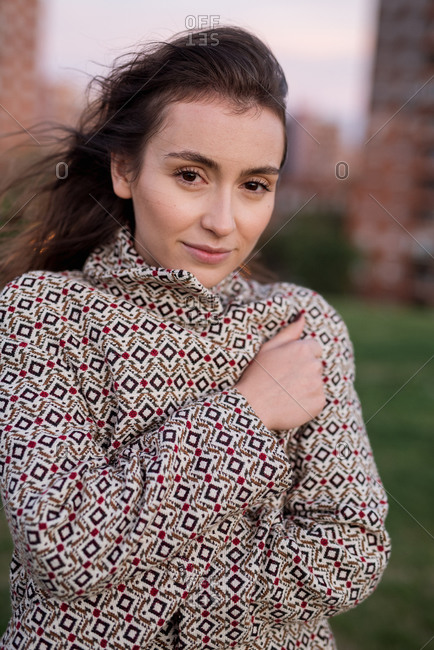 Young brunette standing in cold wind and wrapping in warming jacket looking at camera in Madrid