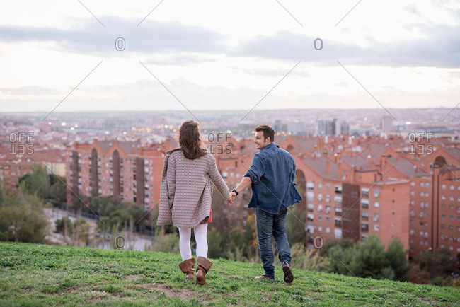 Back view of loving man and woman holding hands while walking on green hill against red buildings of Madrid