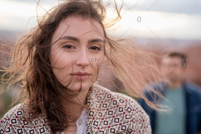 Calm and content woman with brown hair standing and looking at camera with blurred unrecognizable man on background