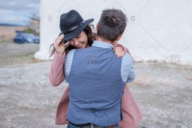 Side view of happy young man in shirt and vest hugging girlfriend in pink coat standing on street in Madrid