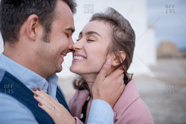 Side view of happy man in shirt and vest hugging and kissing girlfriend with eyes closed in pink coat standing on street in Madrid