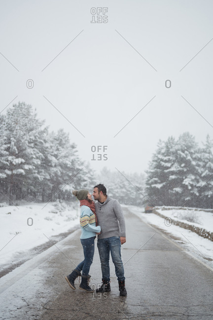 Happy loving man embracing girlfriend while standing on cold empty route in winter haze looking at each other