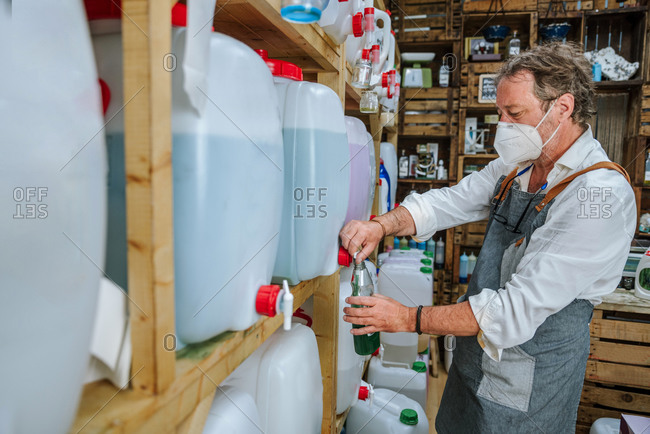 Side view of senior male seller in protective mask and apron filling reusable bottle with detergent while working in eco-friendly shop selling cleaning products