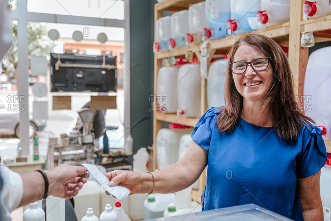 Cheerful mature female client taking receipt from crop anonymous salesman while making purchase in modern zero waste shop selling cleaning products
