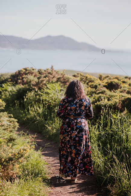 Back view of female in trendy dress walking along sandy pathway near green grass and admiring amazing scenery of lake and mountains
