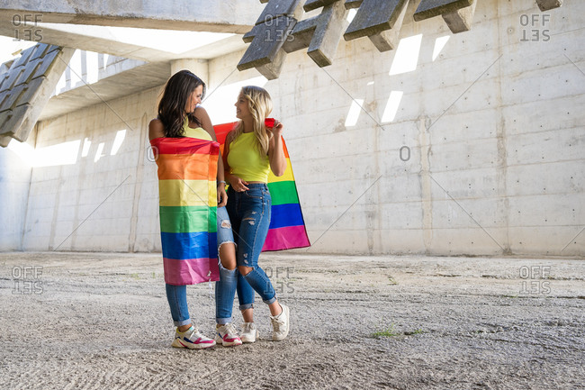 Full body cheerful lesbian couple smiling and looking at each other while wrapping in rainbow flag outside concrete building