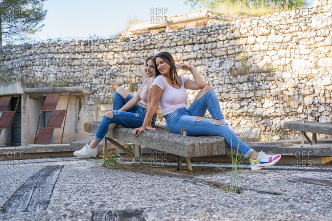 Young women in similar clothes sitting on concrete bench and resting outside stone building in summer