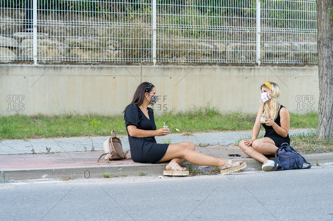 Young women in protective masks sitting on sidewalk and enjoying drinks during quarantine in town