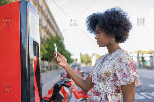 An elegant young African female is using her cellphone app to remotely activate and prepay a rental an electric bicycle