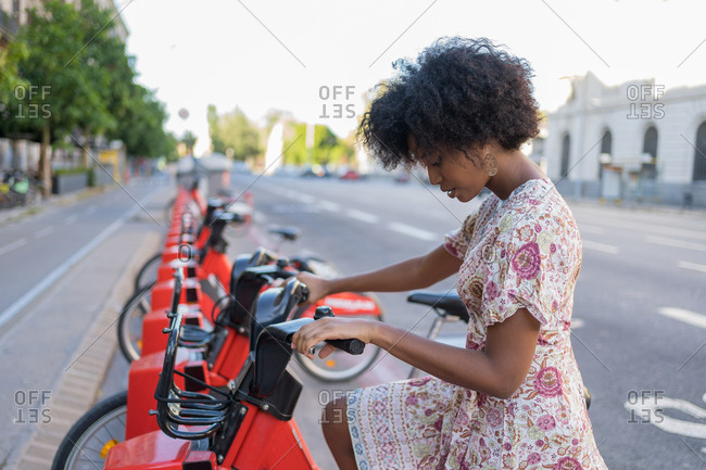 Afro American woman taking a bicycle in a bike sharing platform