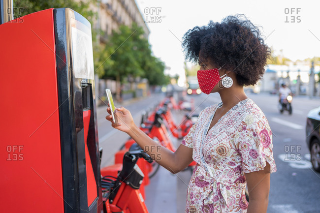 Young African American female with medical mask is using her cellphone app to remotely activate and prepay a rental an electric bicycle