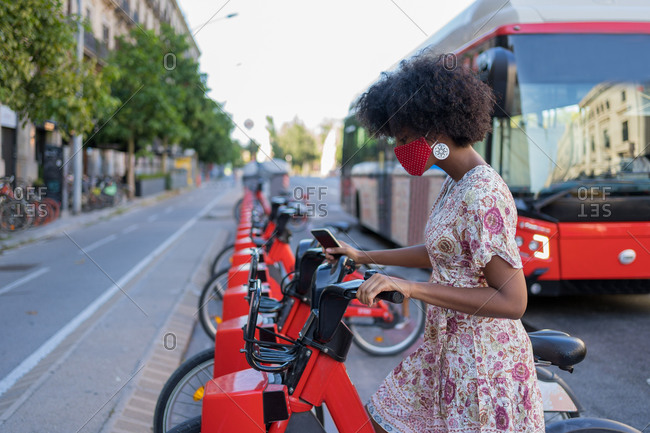 Afro American woman with medical mask taking a bicycle in a bike sharing platform