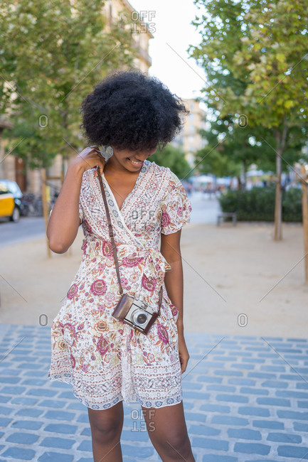 A shy young African-American woman posing with her vintage camera over her shoulder