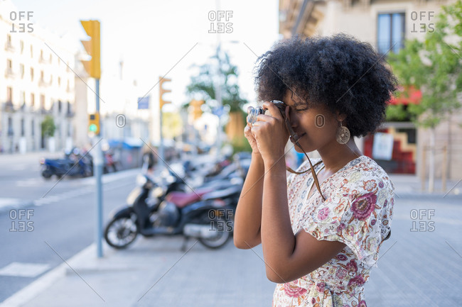 A young mixed race woman with afro hair taking a photo with her analogical camera