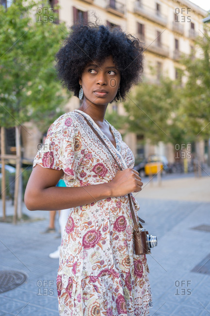 A distracted young African-American woman posing with her vintage camera over her shoulder