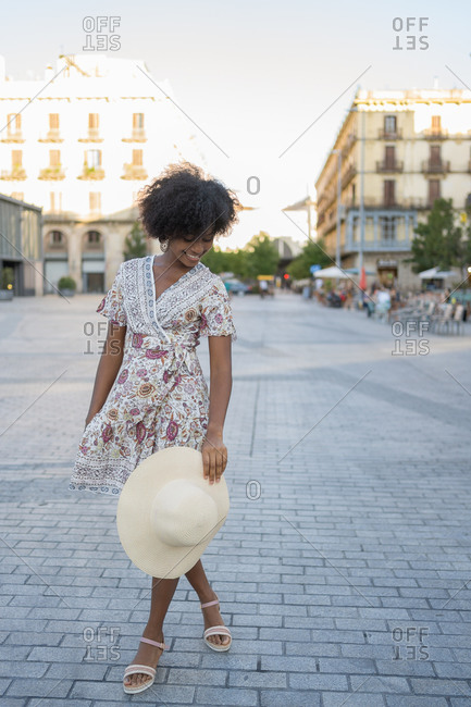 A shy young African-American woman playing with her hat in the middle of the square