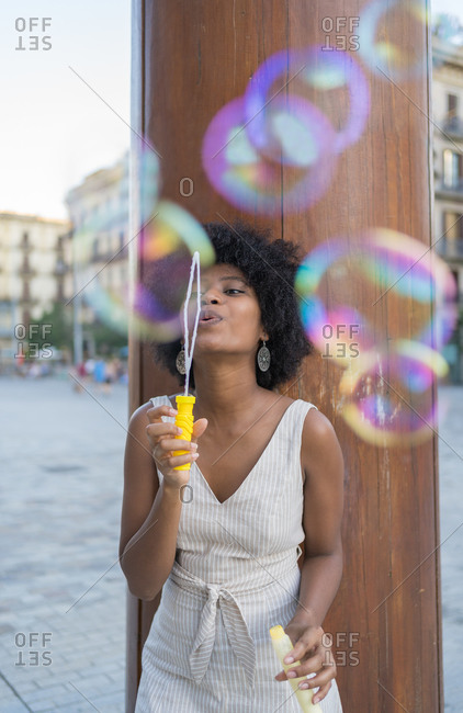 Afro woman blowing soap bubbles in the square