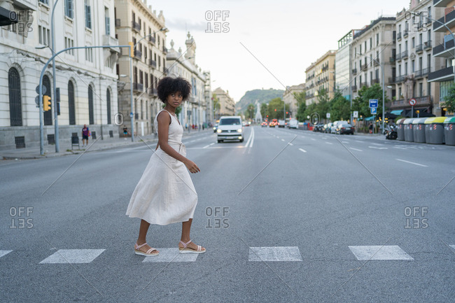 Young Afro-haired woman in a hippie dress crossing the street in fear